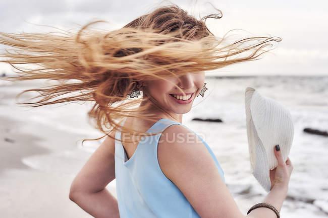 Женщина размахивает волосами на пляже — стоковое фото