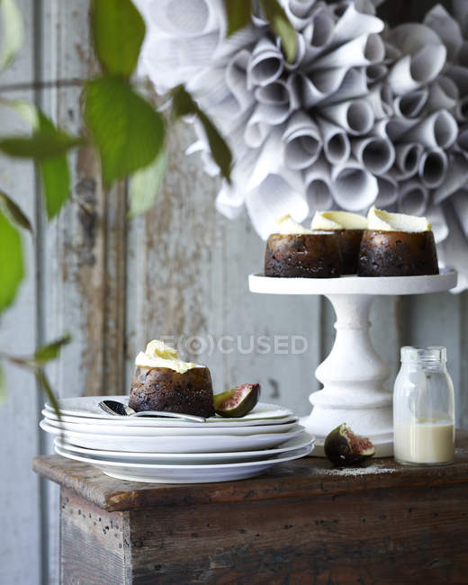 Mini puddings de Noël sur cakestand et assiettes sur table de patio — Photo de stock