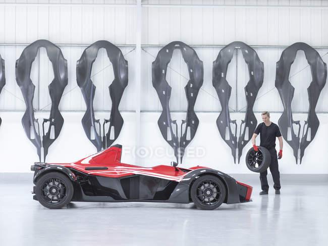 Ingenieur mit Rad um Supersportwagen in Fabrik mit Carbon Fibre Auto Karosserien an Wand — Stockfoto