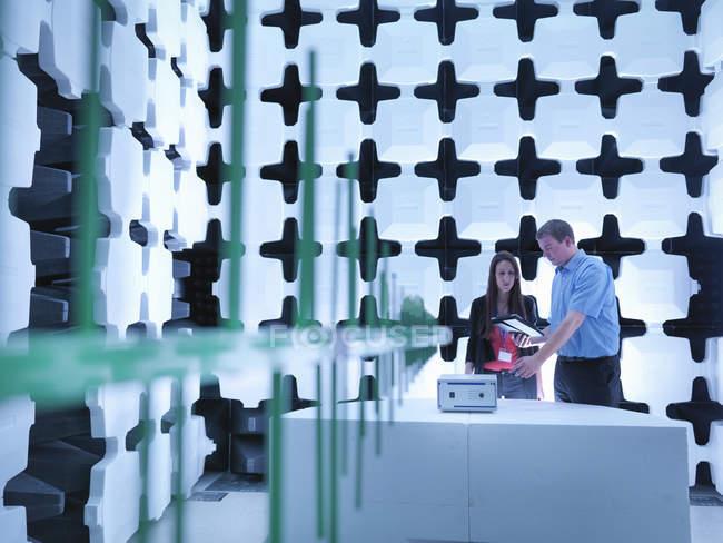 Инженеры проверяют тестируемое оборудование (Eut) в полуанехоической камере с энергетическими поглотителями и билоговой антенной, созданной для электромагнитной совместимости (Emc) излучаемого испытания иммунитета — стоковое фото