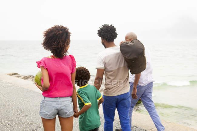 Rear view of family of four strolling along Ipanema beach, Rio De Janeiro, Brazil — Stock Photo