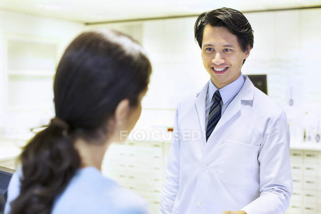Male pharmacist handing prescription to customer — Stock Photo
