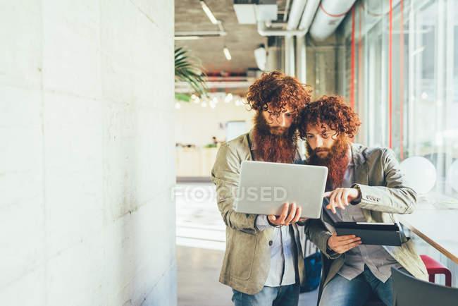 Дорослого чоловічого hipster близнюків, вказуючи на ноутбуці в офісі — стокове фото