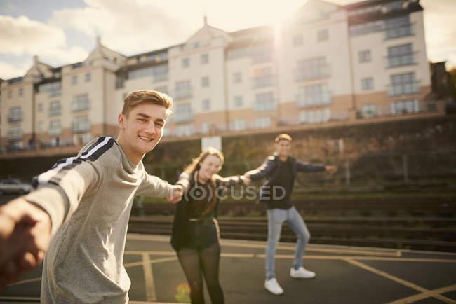 Tre amici che ingannare intorno all'aperto, tenendosi per mano, Bristol, Regno Unito — Foto stock