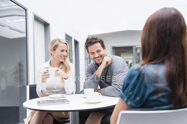 Collègues d'affaires riant avec le café dans le bureau — Photo de stock