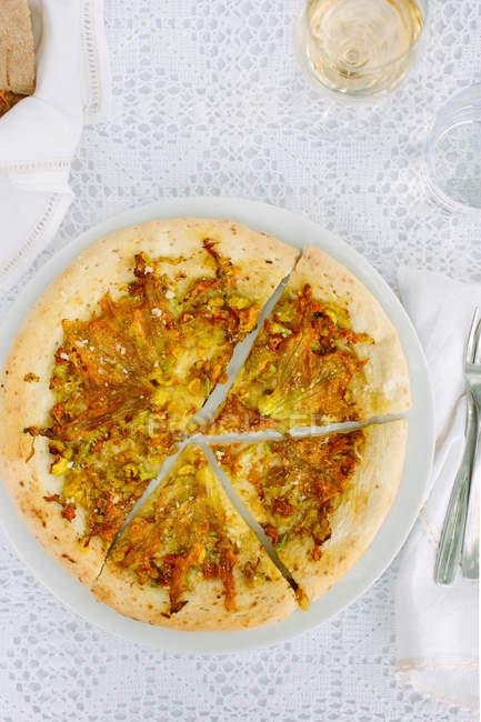Mesa al aire libre pizzas de masa fina rústica con flores de calabacín y queso scamorza, Cilento, Italia - foto de stock