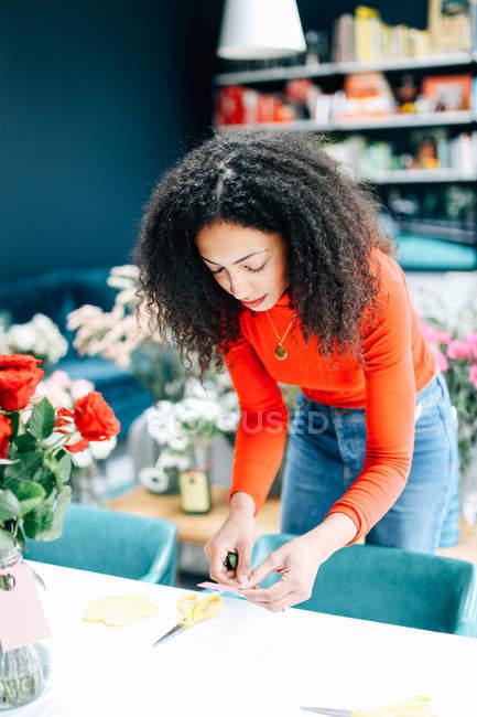 Жіночий флорист готує етикетки для квітів організація семінару — стокове фото