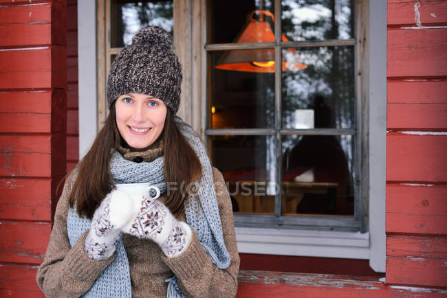 Portrait of young woman drinking coffee in front of cabin, Posio, Lapland, Finland — Stock Photo