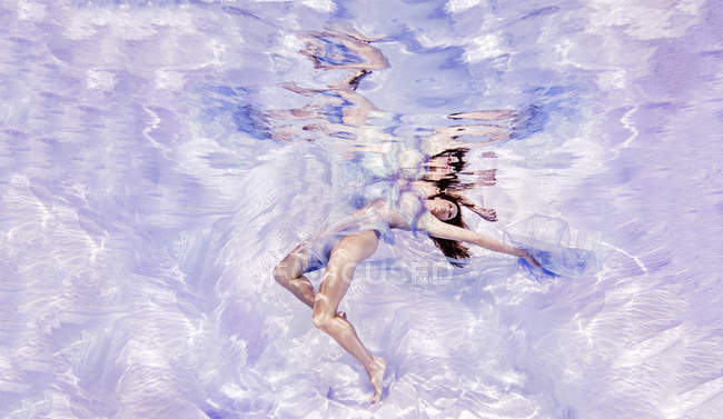 Vue sous-marine de la femme drapée de tissu transparent, flottant vers la surface de l'eau — Photo de stock