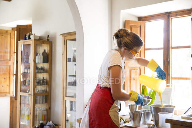 Young woman pouring liquid lavender soap into bowl in handmade soap workshop — Stock Photo