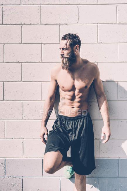 Молодий оголеними грудьми чоловіки хрест тренер її до стіни за межами тренажерного залу — стокове фото