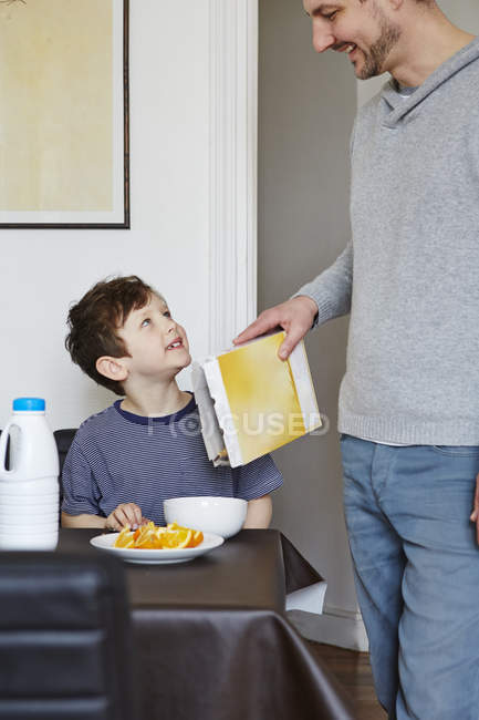 Father pouring cereals into son breakfast bowl — Stock Photo