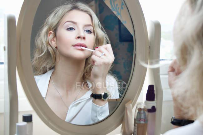 Ragazza adolescente guardando allo specchio, applicando il make-up — Foto stock