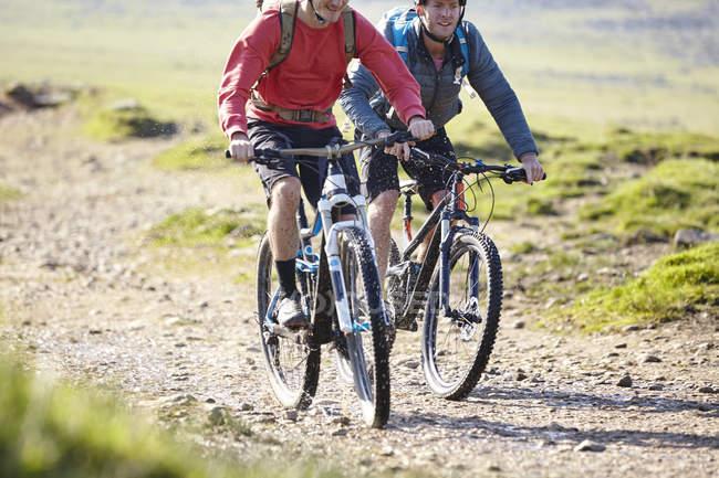 Велосипедистов велосипеде вниз грунтовой дороге — стоковое фото