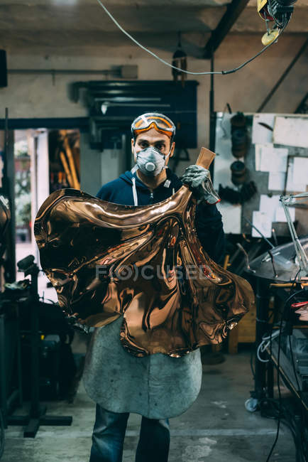 Portrait of metalworker holding copper product in forge workshop — Stock Photo