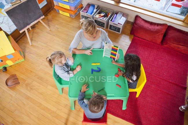 Vista aerea di insegnanti e alunni che contano alla scuola materna — Foto stock