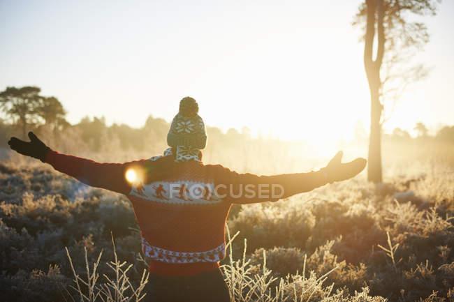 Rückansicht des Mannes in Winterkleidung mit offenen Armen in der Sonne — Stockfoto