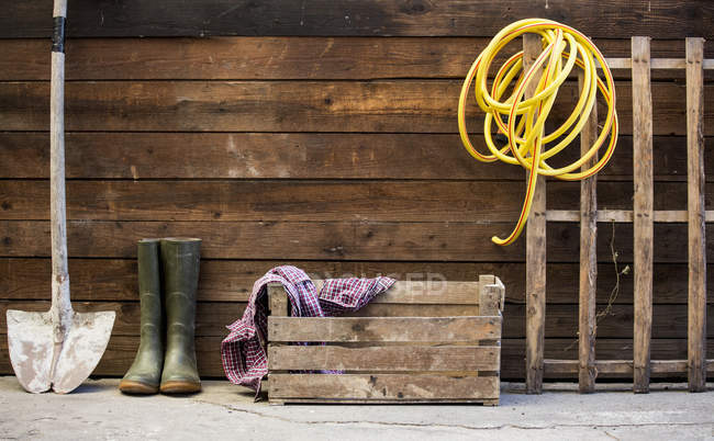 Row of spade, rubber boots and hosepipe by shed — Stock Photo