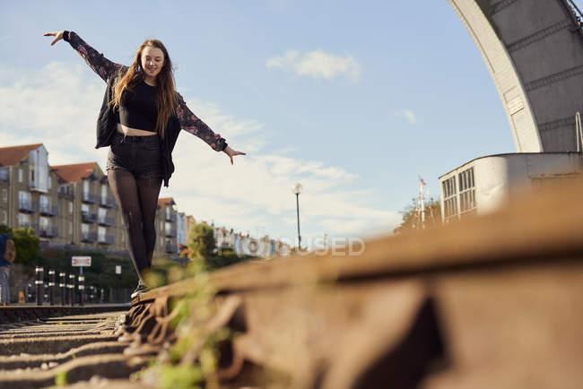 Giovane donna in equilibrio sul binario del treno, vista a basso angolo, Bristol, Regno Unito — Foto stock