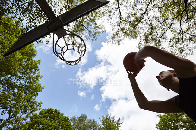 Low angle view of silhouetted young man aiming ball at basketball hoop — Stock Photo