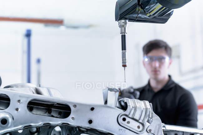 Apprentice engineer measuring car body in car factory — Stock Photo