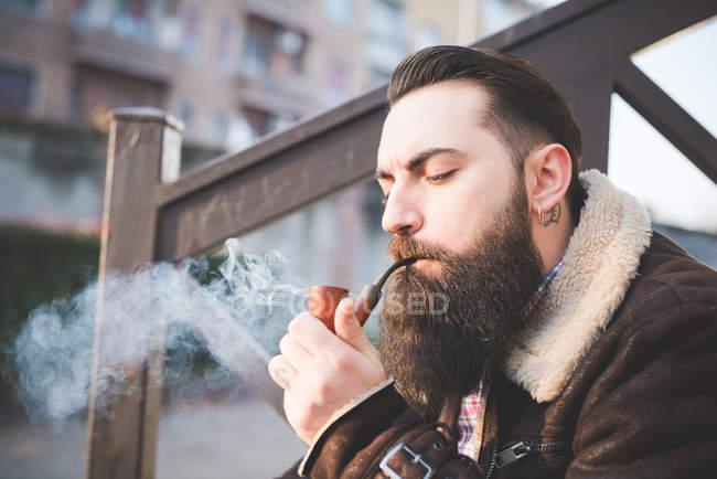 Guapo hombre con barba fumando cigarrillo electrónico - foto de stock