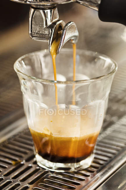 Close up of coffee machine pouring coffee into glass — Stock Photo