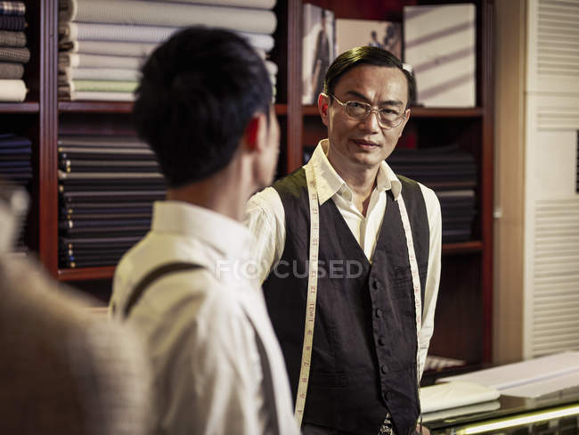 Father talking to son in family tailoring business — Stock Photo