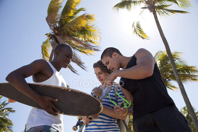Young man holding skateboard with friends, low angle — Stock Photo