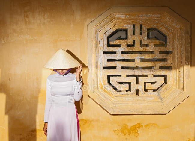 Середині дорослу жінку носити сукні Дая АО і В'єтнамську капелюх, що стоїть перед стіни, дивлячись вниз, Хюе, В'єтнам — стокове фото