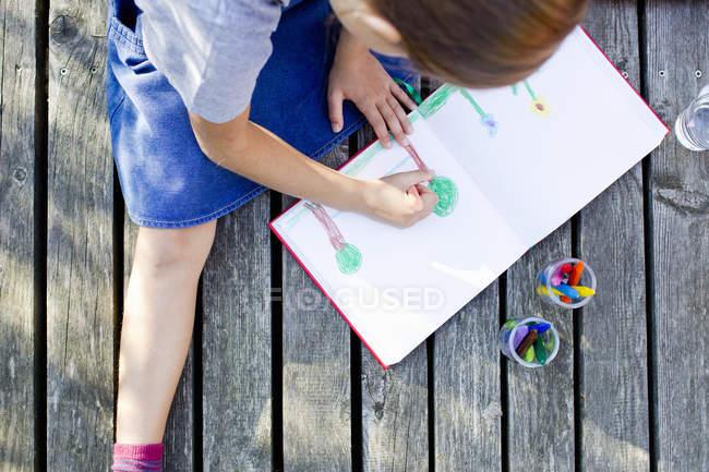 Дівчина малюнок малюнок у блокноті, висока кут — стокове фото