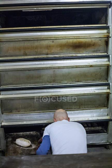 Opinião traseira o padeiro do homem no forno na padaria — Fotografia de Stock