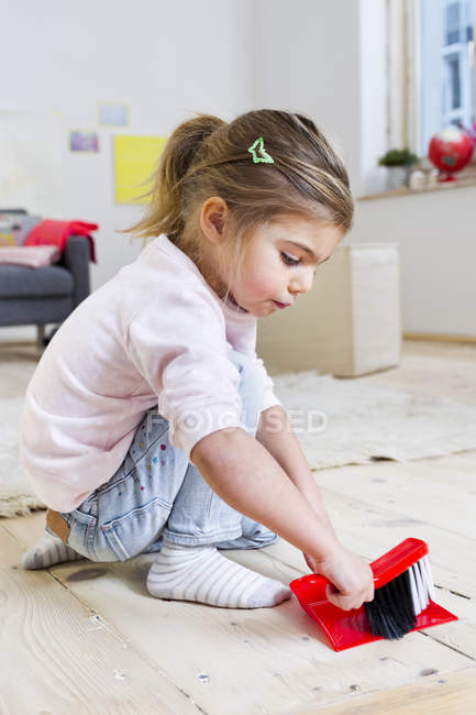 Girl sweeping floor with brush at home — Stock Photo