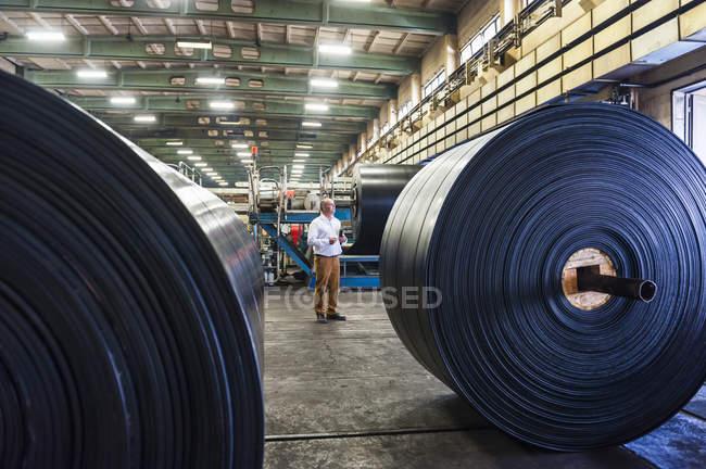Чоловік працівник в гумовому Роликовий завод — стокове фото