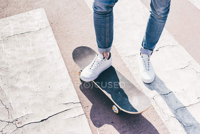 Legs and feet of young male skateboarder on pedestrian crossing — Stock Photo