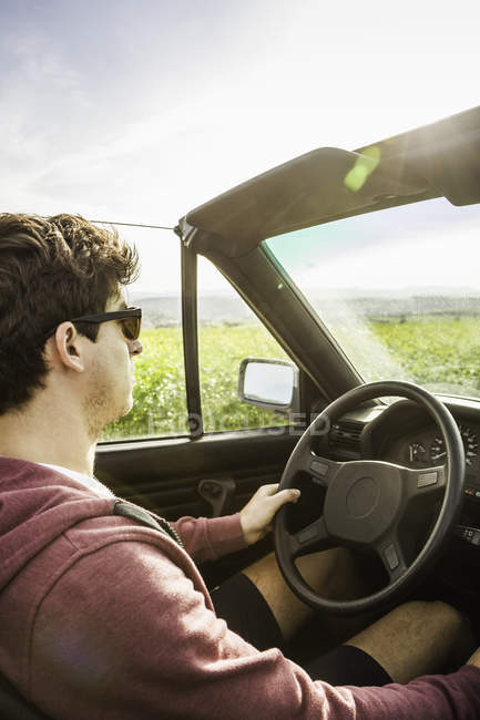 Young man leaning driving convertible — Stock Photo