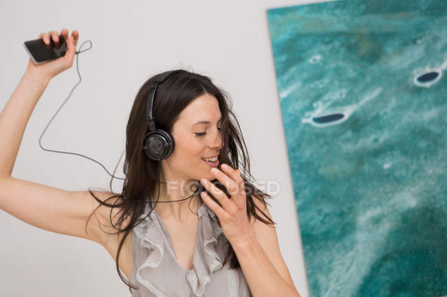 Mid adult woman listening to music through headphones — Stock Photo