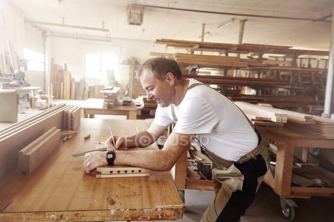 Vue latérale du charpentier d'homme insérant la douille en bois à l'établi — Photo de stock