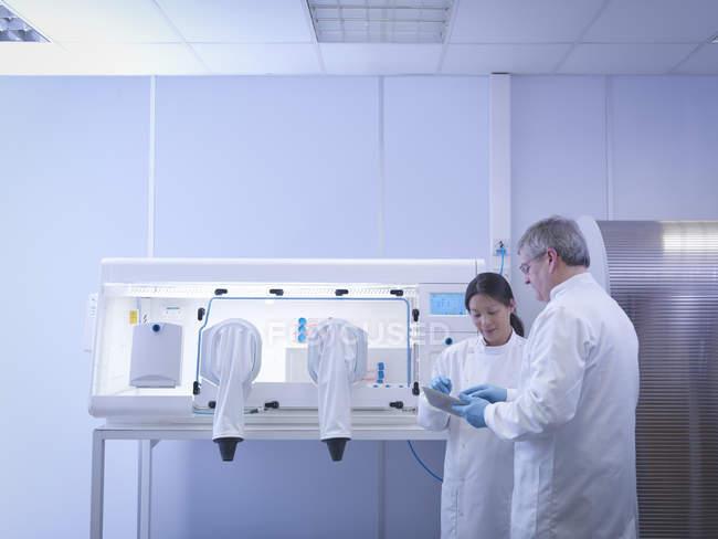 Scientifiques discutant des notes dans le laboratoire à côté du poste de travail de laboratoire — Photo de stock