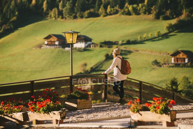 Femme avec vue par une barrière en bois, Santa Maddalena, Dolomite Alps, Tyrol du Sud, Italie, Val di Funes (vallée de Funes) — Photo de stock