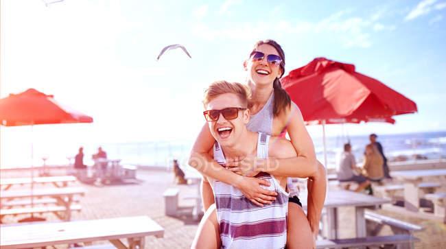 Man giving smiling woman piggyback — Stock Photo