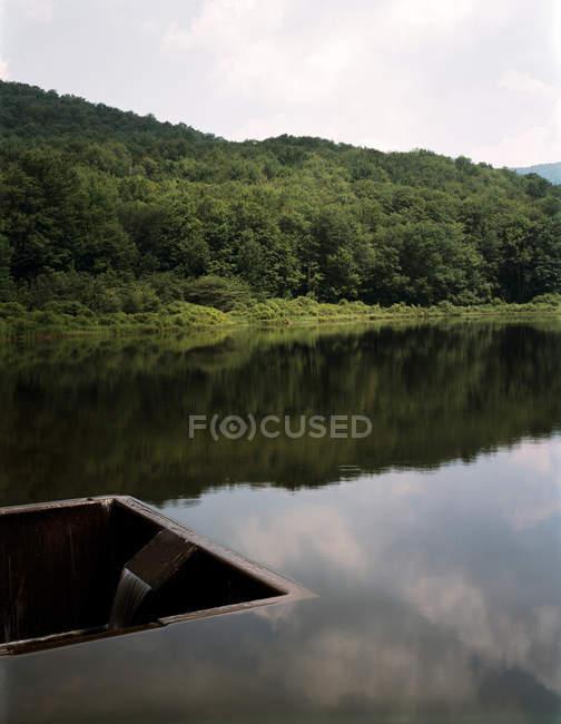 Collina rurale riflessa nel lago — Foto stock