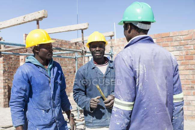 Африканские строители говорят на строительной площадке — стоковое фото