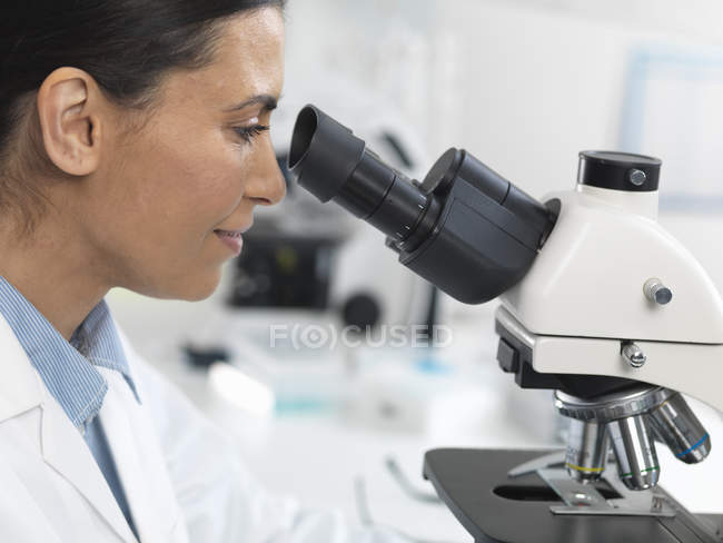 Female scientist viewing sample slide for clinical test in laboratory — Stock Photo
