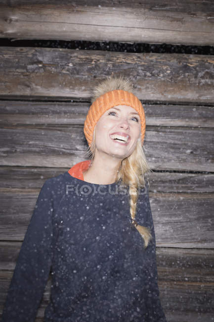 Portrait of young woman in orange knit hat looking up — Stock Photo