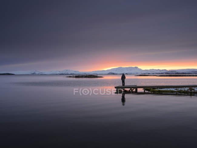 Uomo in piedi sul molo di lago guardando il tramonto, Thingvellir, Islanda — Foto stock