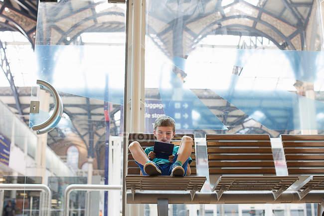 Молодий хлопчик залізничного вокзалу приймальня гра портативний гра — стокове фото