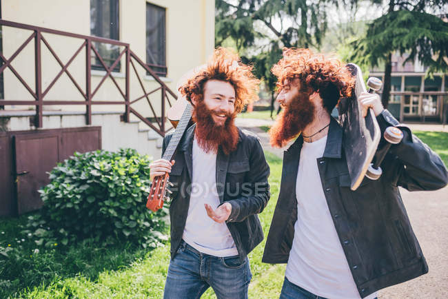 Young male hipster skateboarder twins with red beards strolling in park — Stock Photo