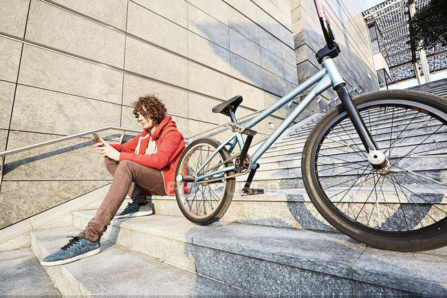 Homem sentado em passos com BMX usando smartphone — Fotografia de Stock