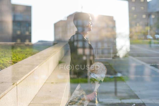 Reflejo de ventana del skate boarder urbano masculino joven - foto de stock